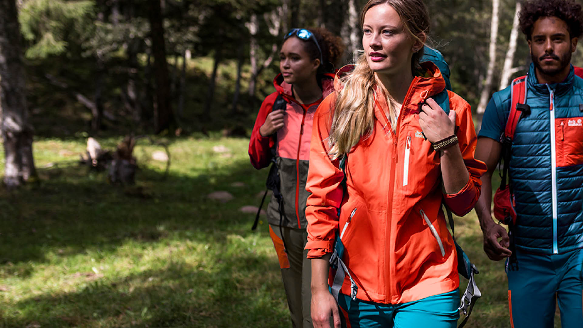 Woman and Men are wearing Jack Wolfskin Backpack and Jacket in ornage and blue