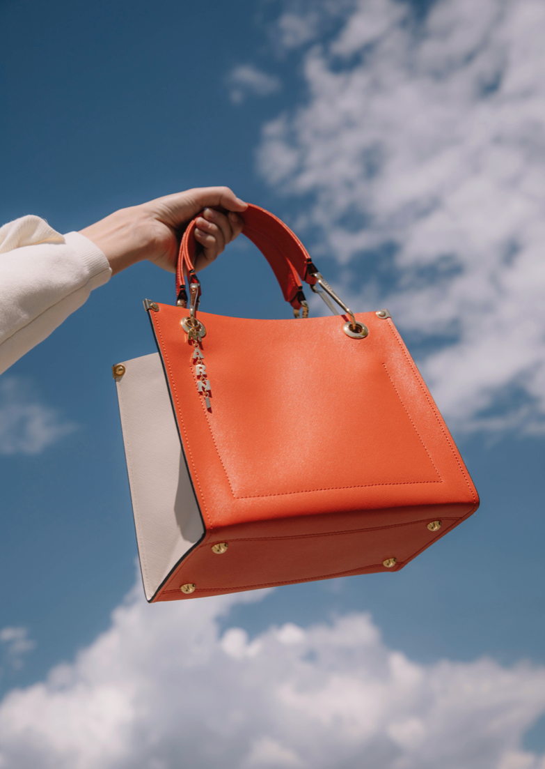 Woman holding an orange bucket bag from Marni