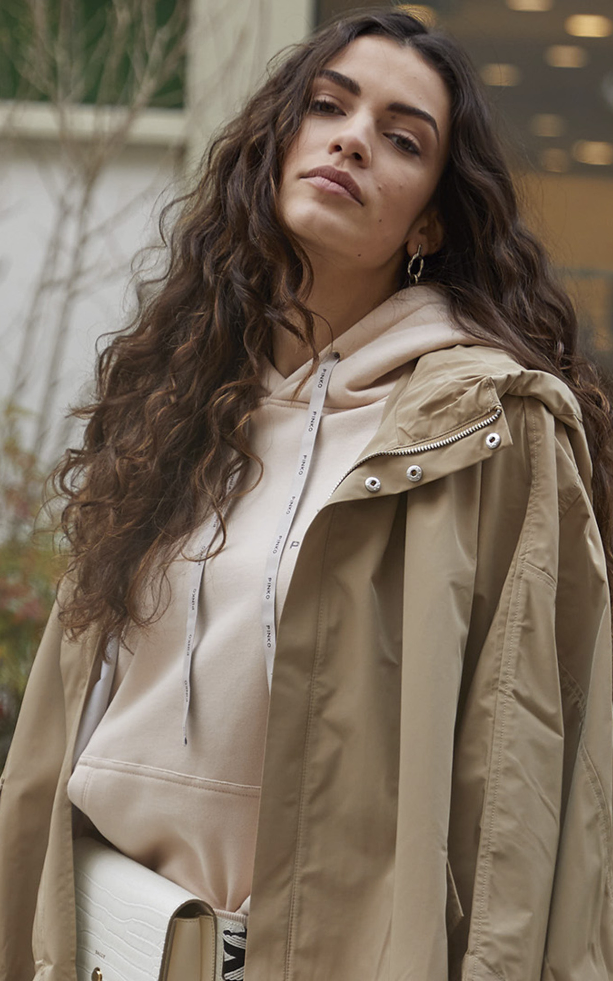 Girl with a beige trench and a beige hoodie at La Roca Village