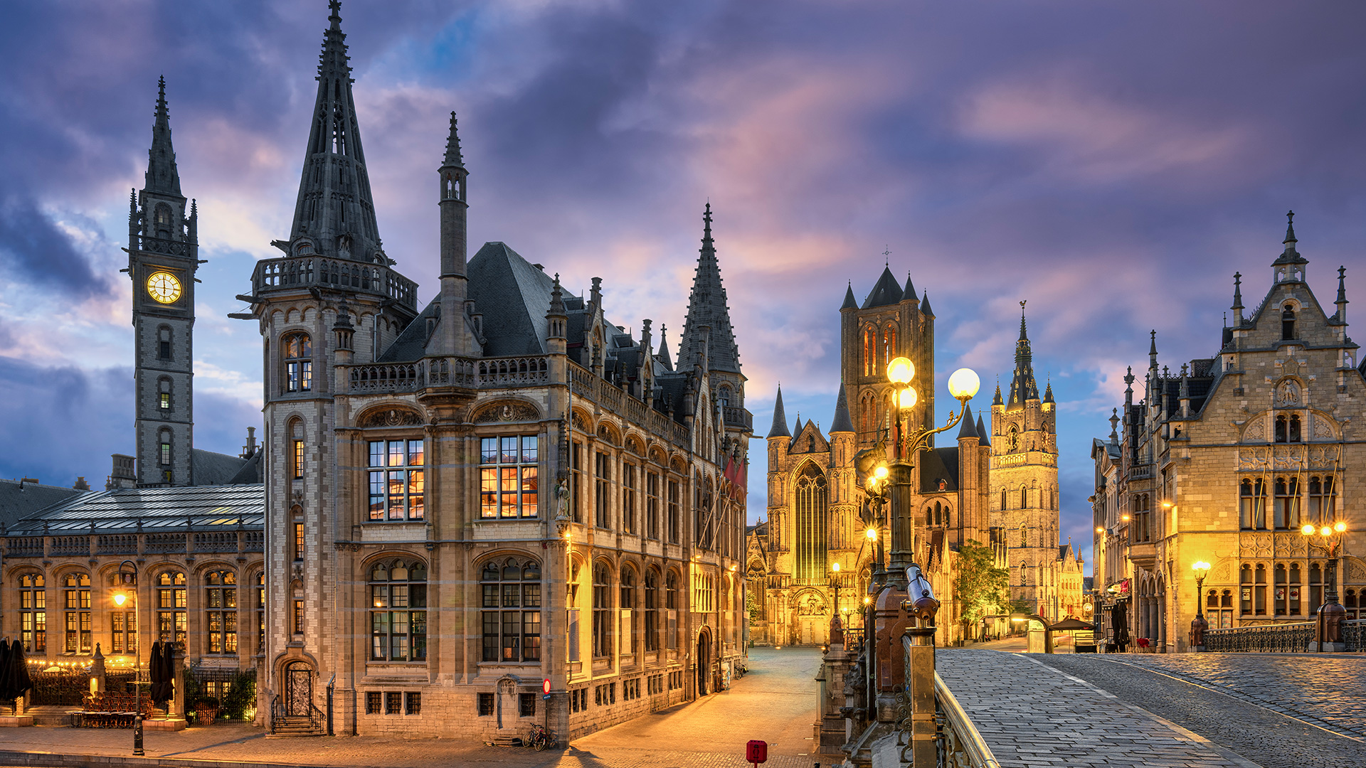 View of historic area of Graslei and bell tower at River Leie and bridge Sint-Michielsplein at dusk, Ghent, Belgium