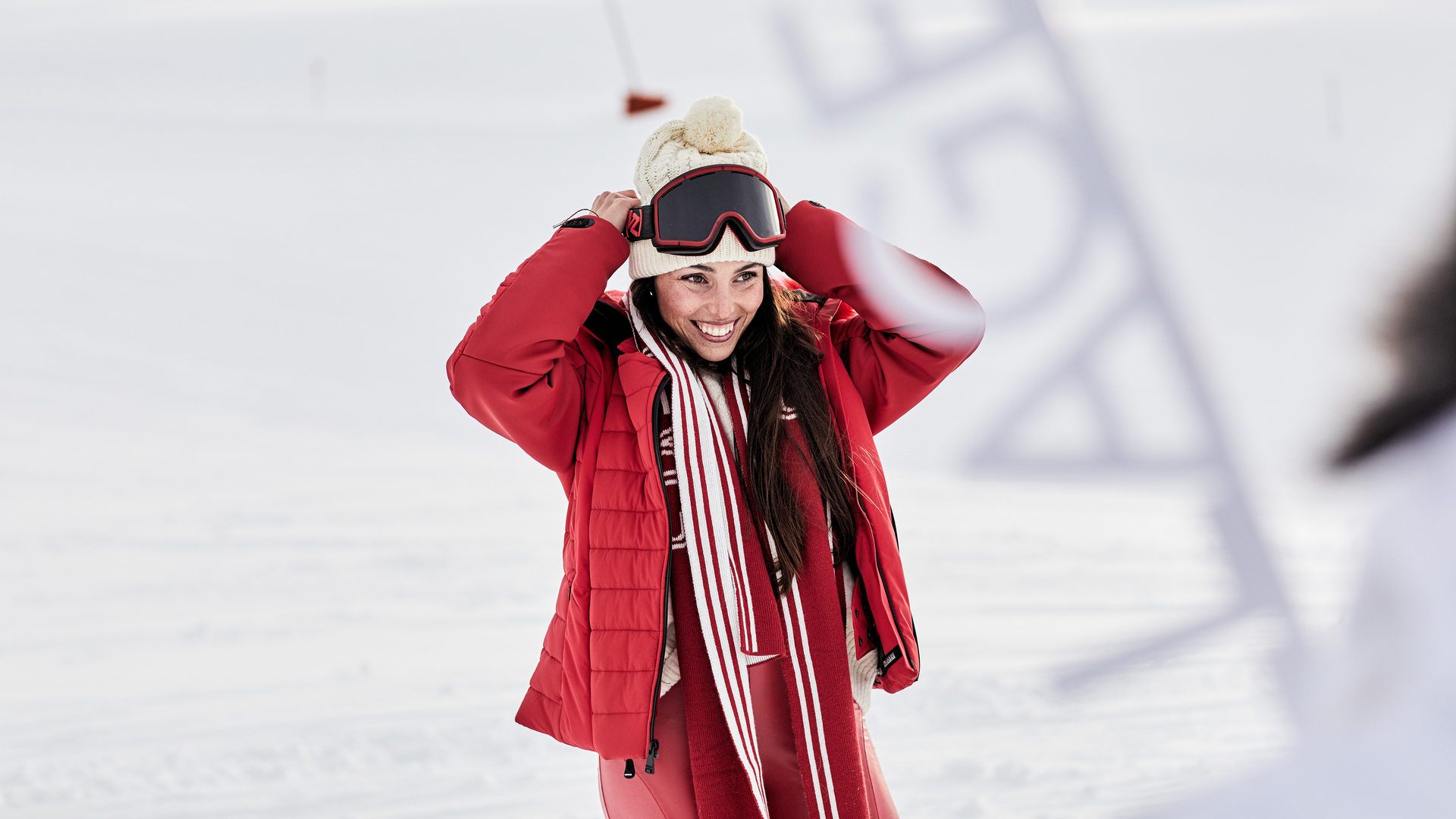 Woman with red jacket smiling in the snow