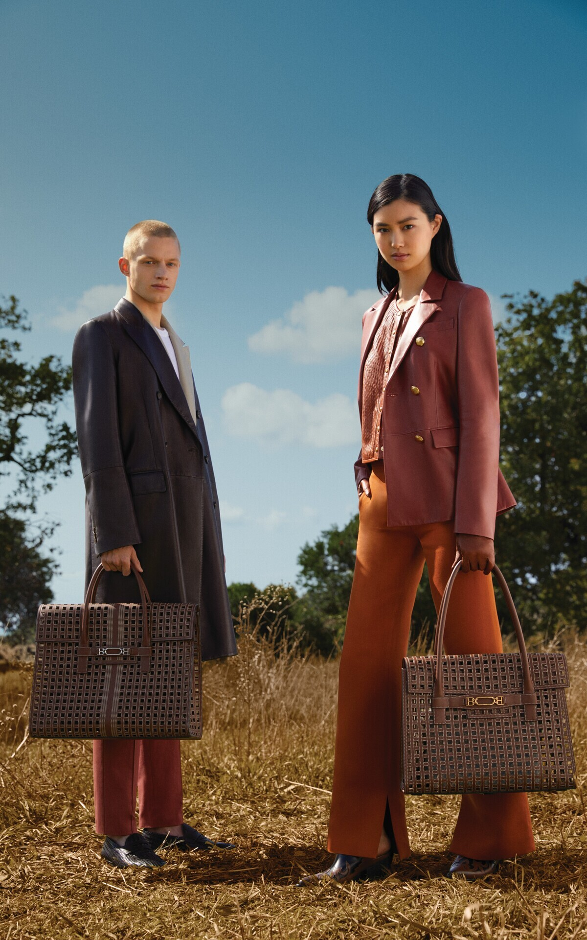 Man and woman in the countryside with Bally jackets and bags