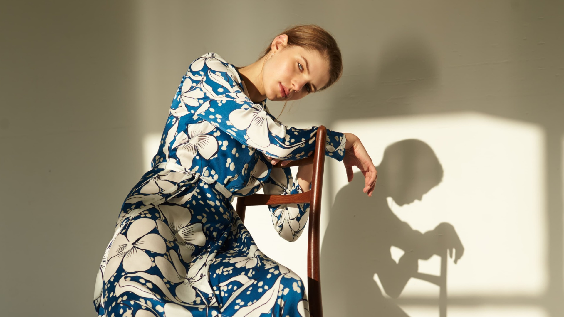 Woman with a blue printed dress sitting on a chair