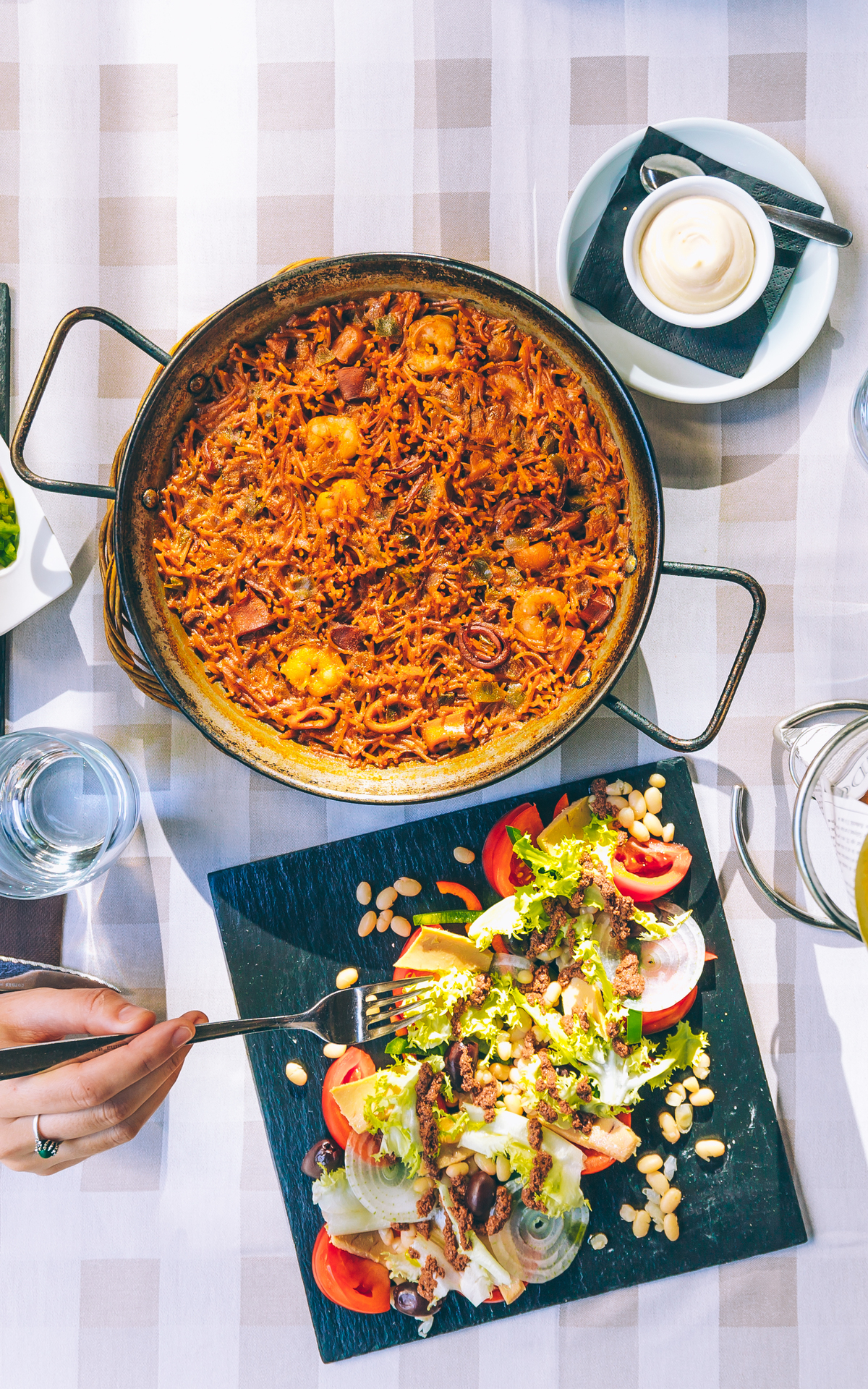 Table with paella and Mediterranean salad