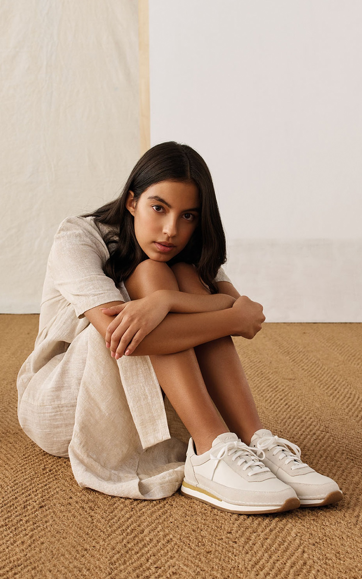 Girl on the floor with a clarks sneakers