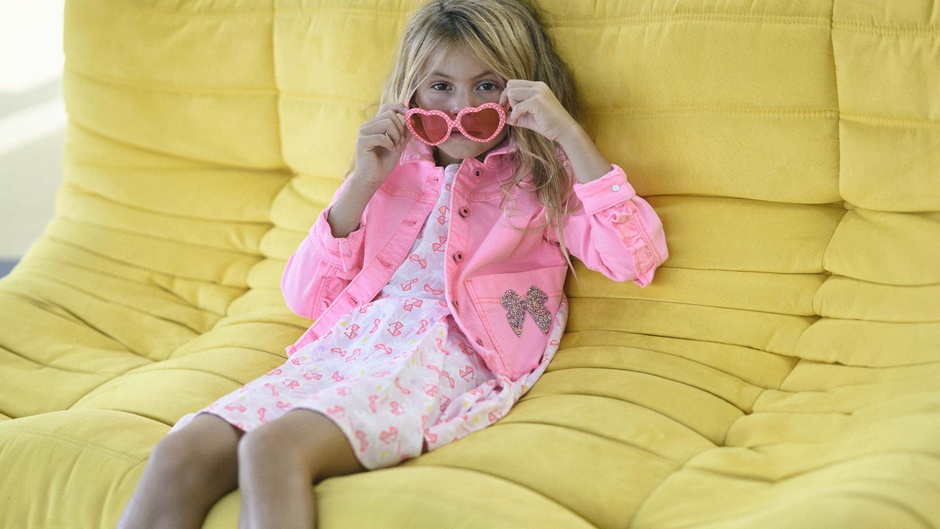 Girl in a yellow sofa with a pink dress
