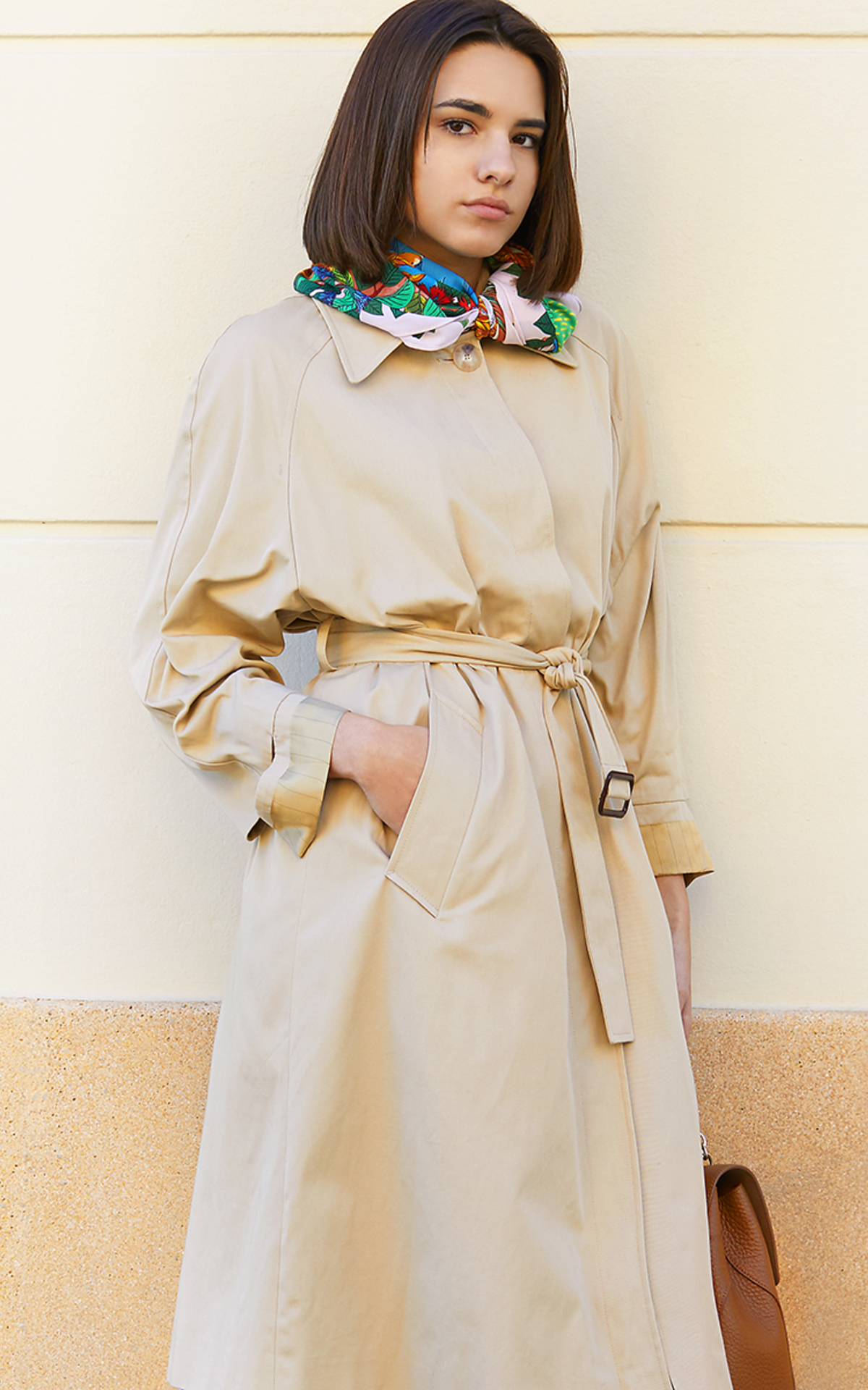 Woman wearing a camel coat and sunglasses