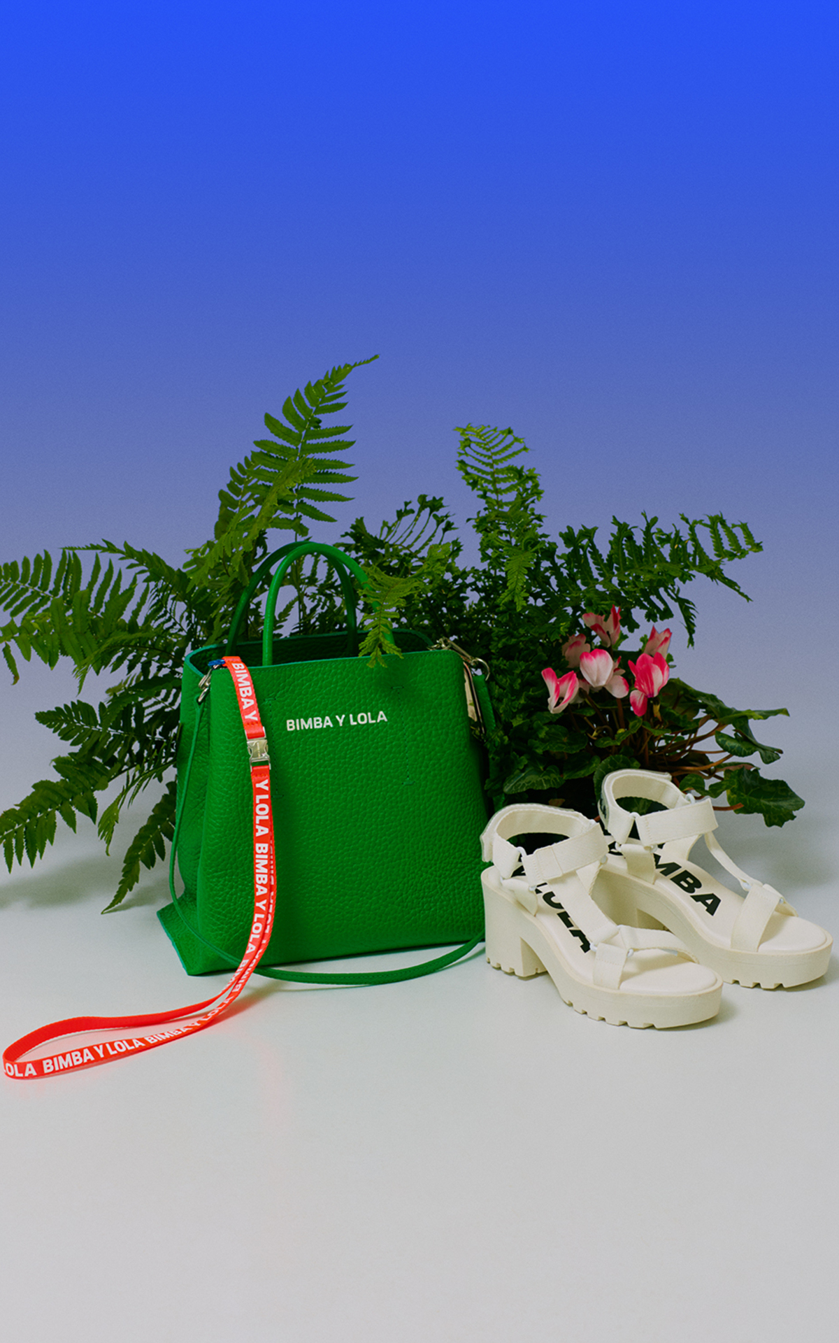 Green bag and white sandals with a background with plants Bimba y Lola