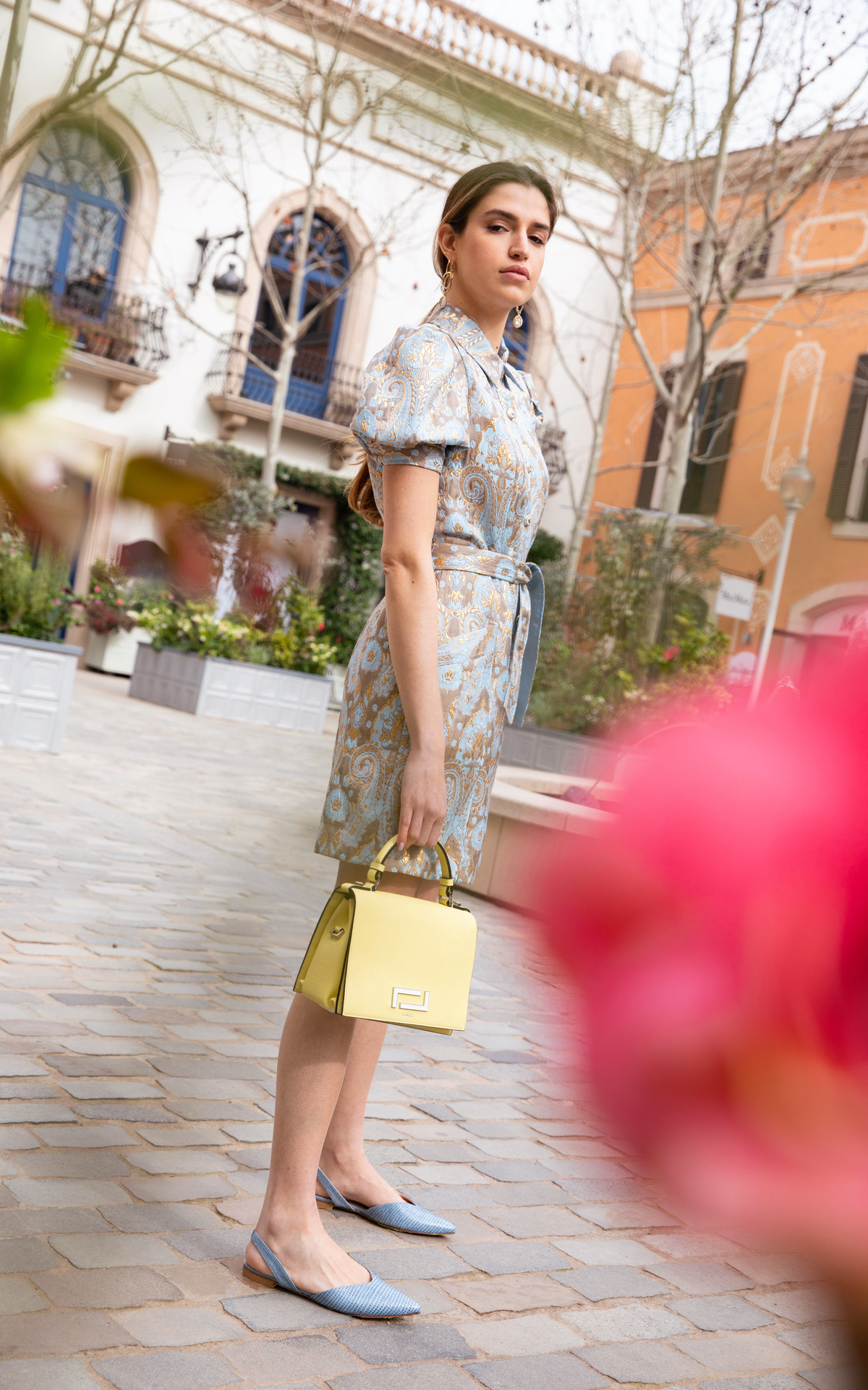 Woman with a printed baby blue dress holding a yellow bag
