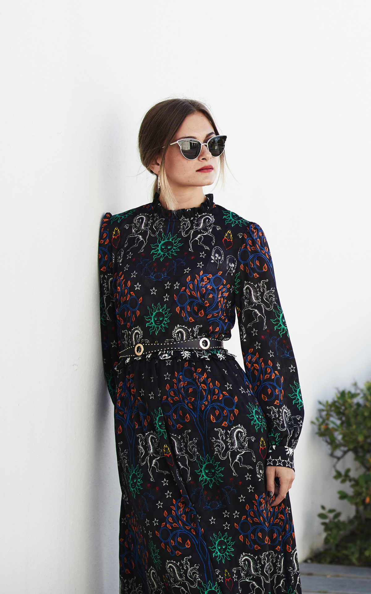 Woman leaning on the wall with sunglasses and a printed dress
