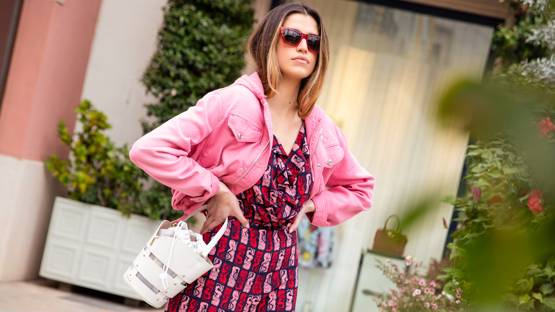 Blonde woman wearing a pink printed jumpsuit and sunglasses