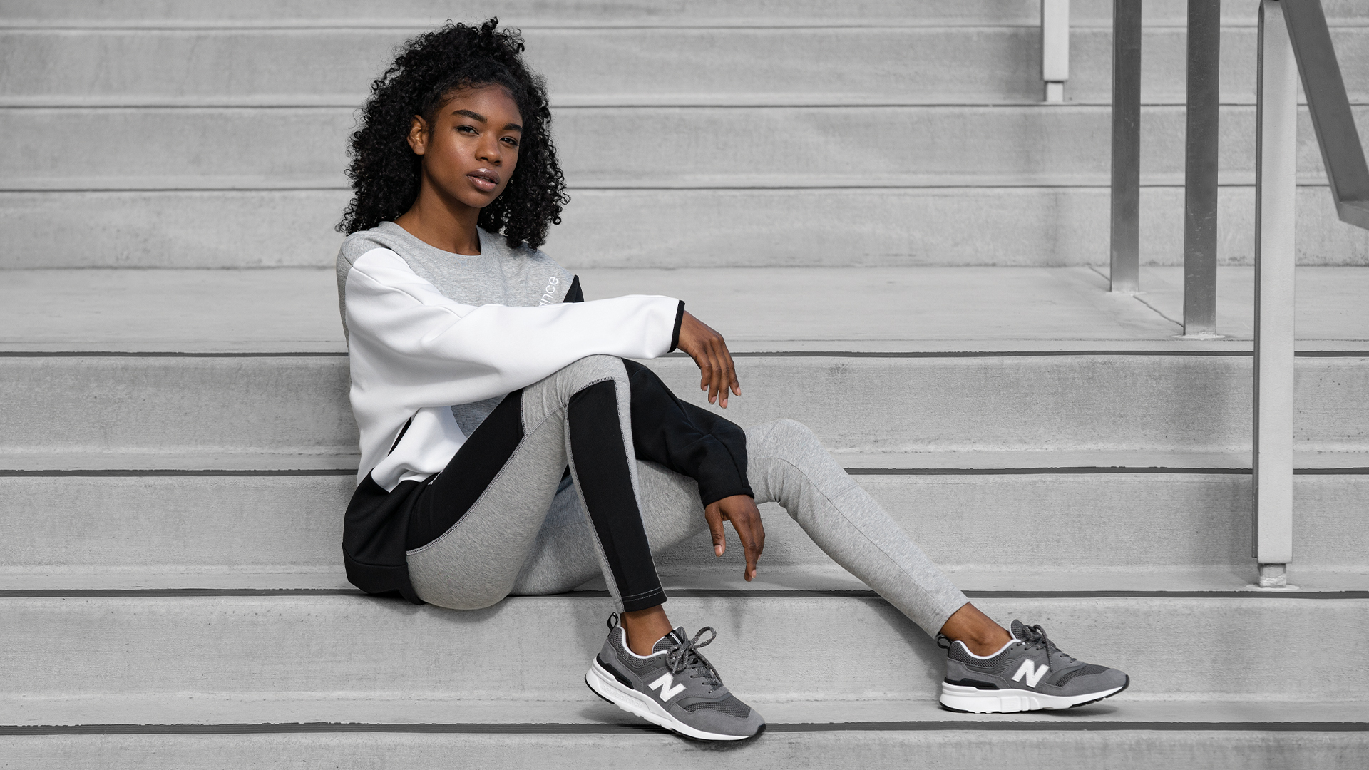 Woman with New Balance sneakers sitting on stairs