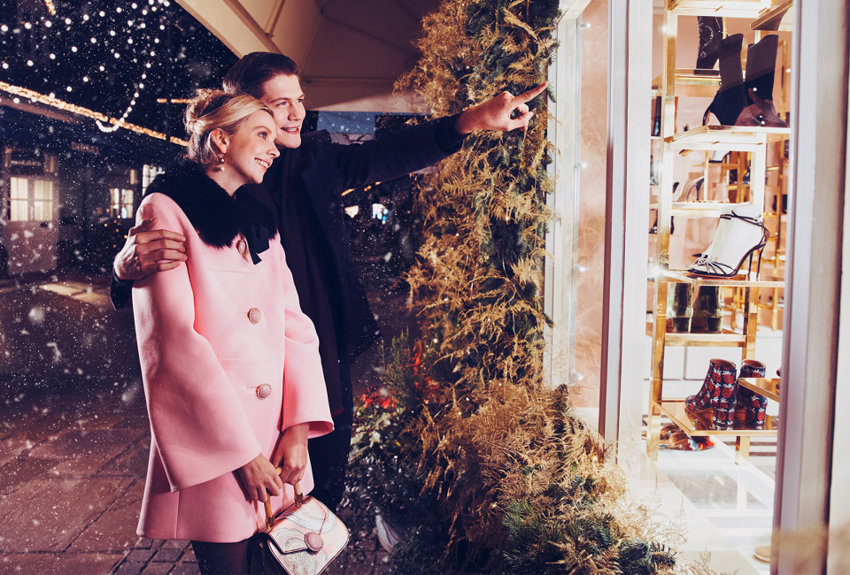 Lady and man window shopping in snow at Christmas at Bicester Village