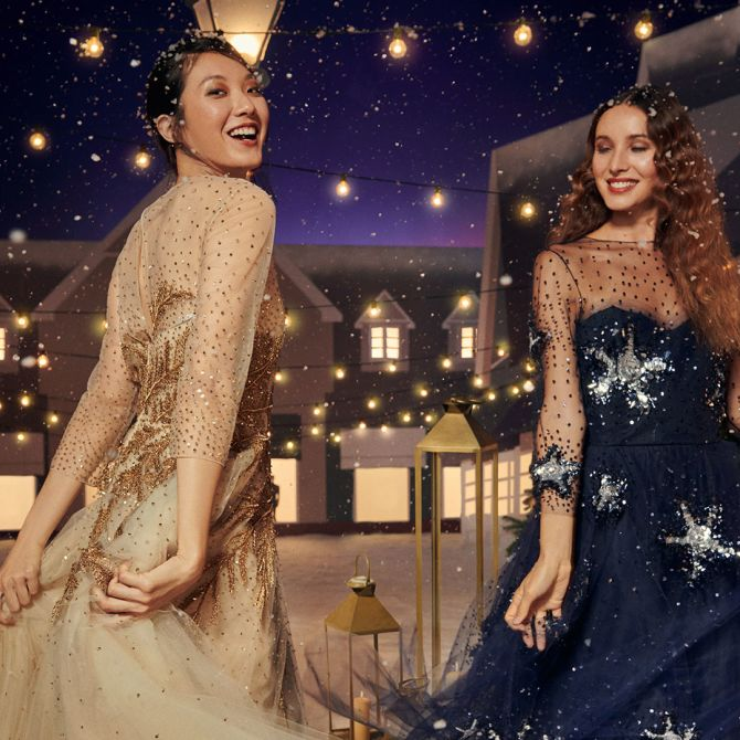 Two women dancing in a winter wonderland wearing beautiful dresses