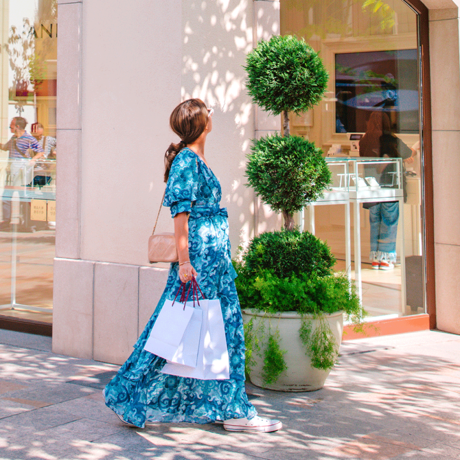Woman wearing a blue dress and shopping at La Roca Village