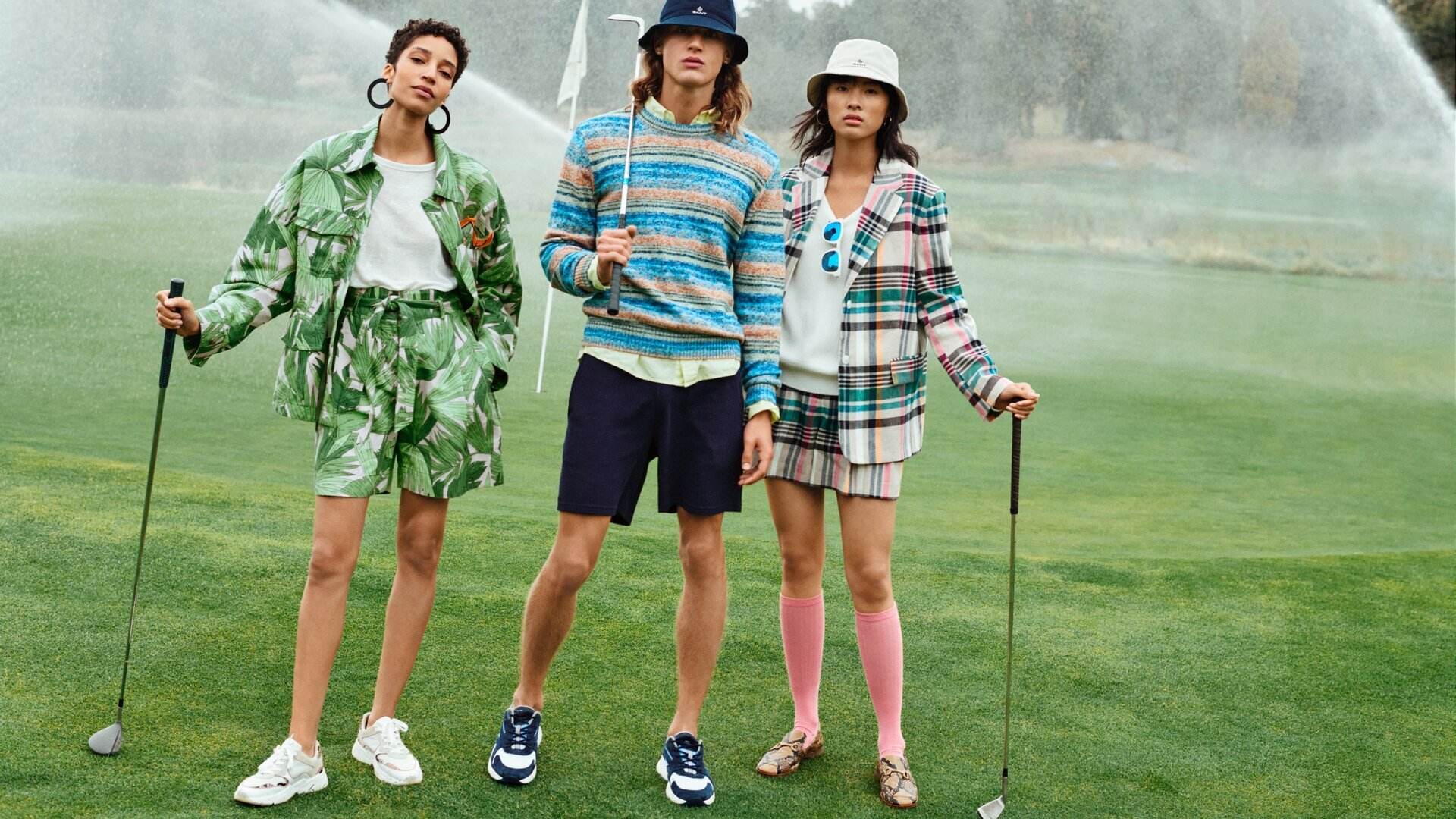 2 girls and a boy playing golf
