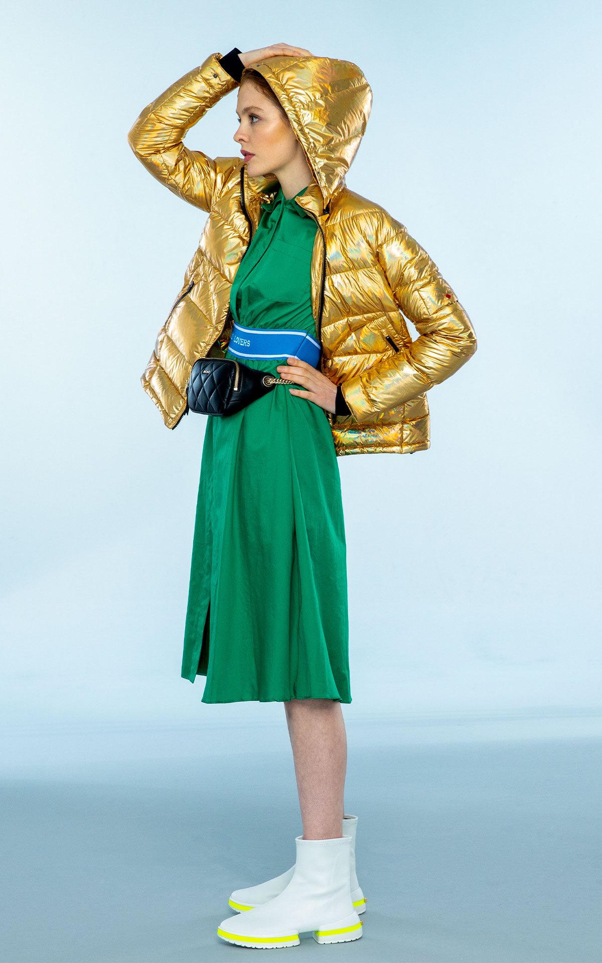 Womenswear new arrivals lady in gold coat and green dress at Bicester Village