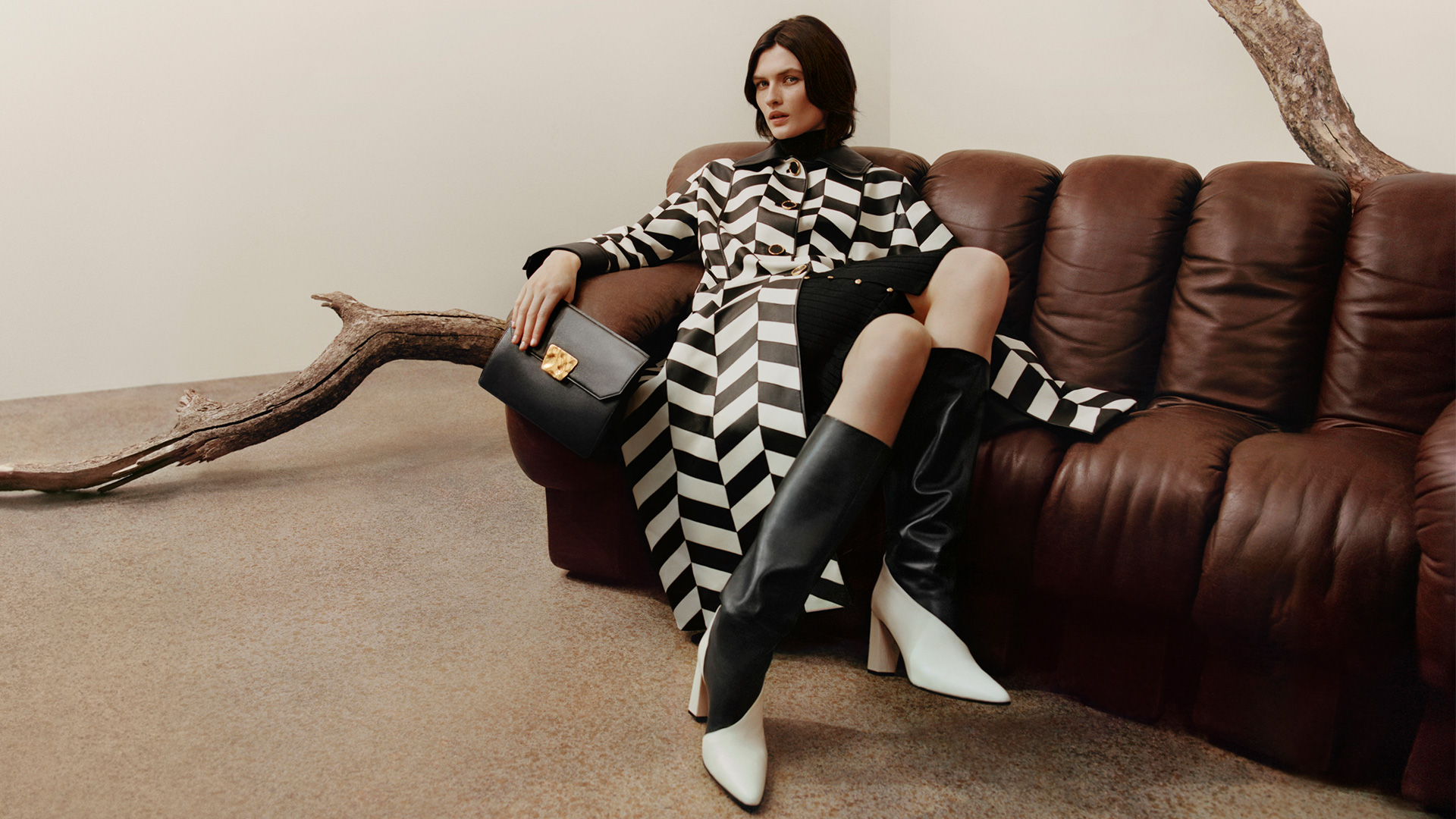 Woman with a black and white checked coat in a sofa