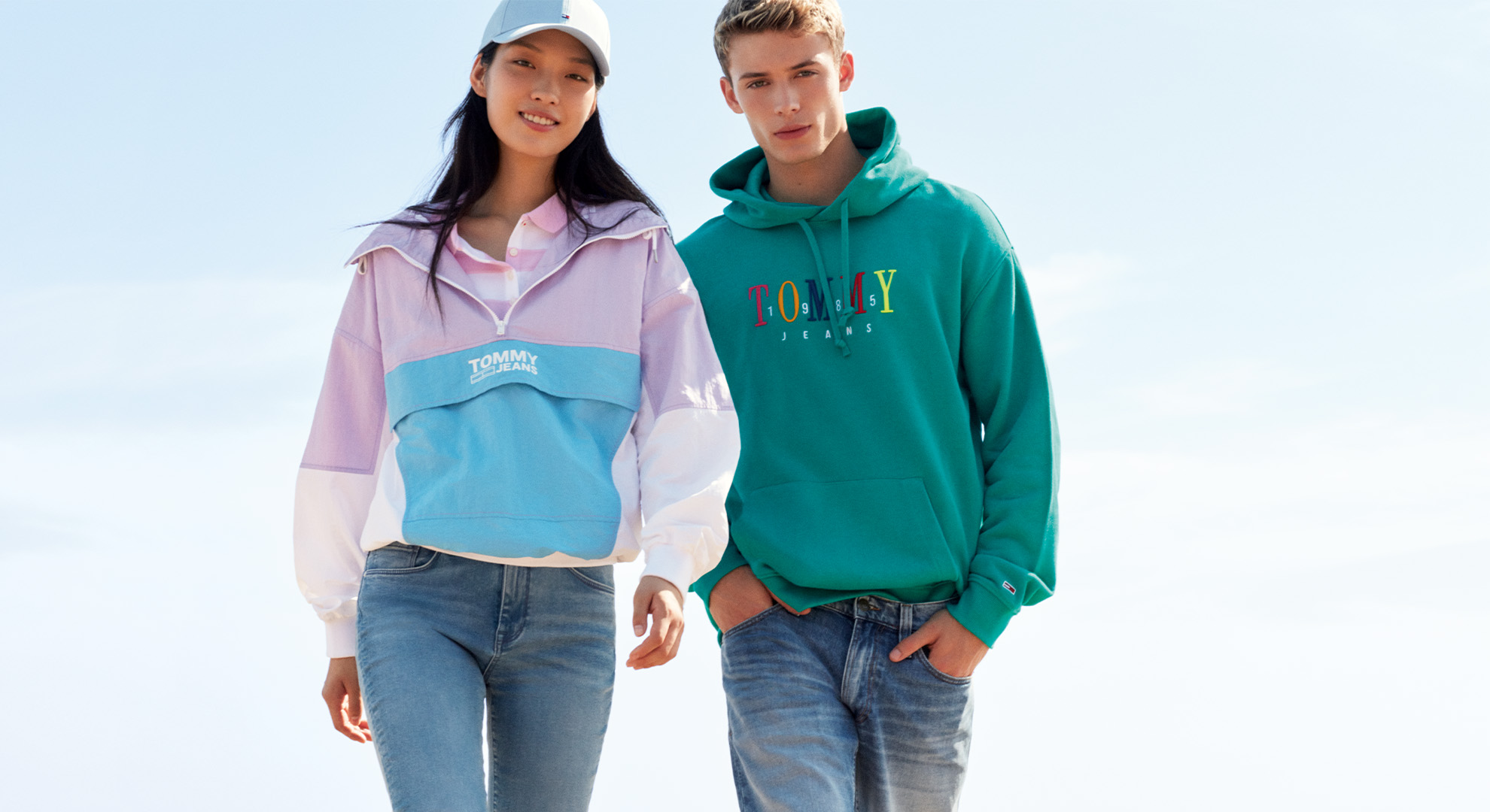 Man and woman walking on the beach in Tommy Hilifiger clothing