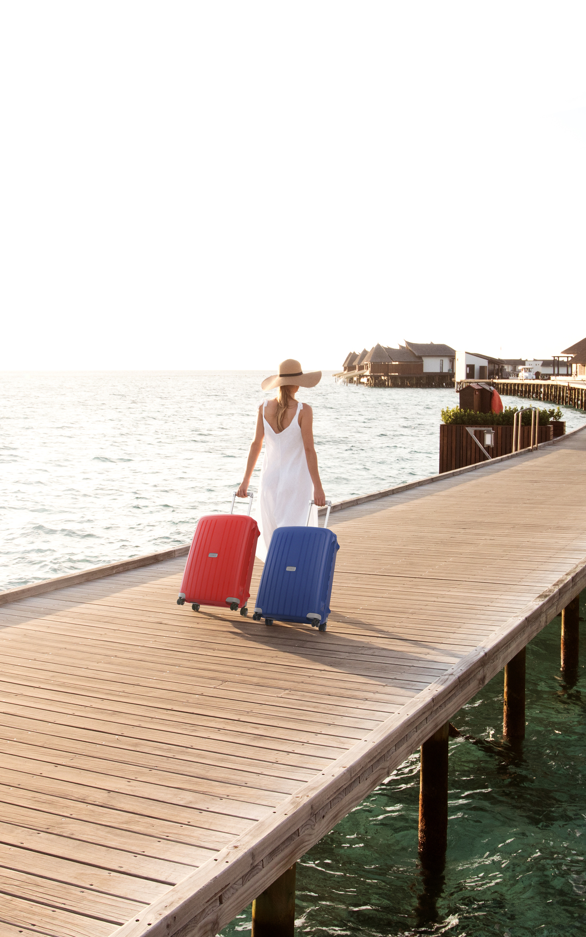 Woman with a blue and red suitcases Samsonite in Maldivas