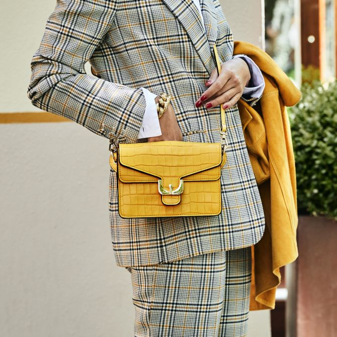 Girl dressed with a grey suit and yellow bag